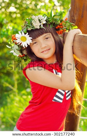 little girl with a wreath of wild flowers