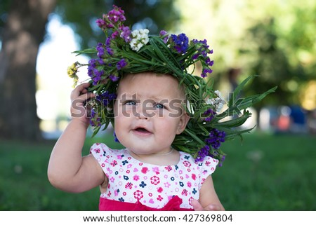Little girl with a wreath on a head and bouquet in hands on a glade from dandelions