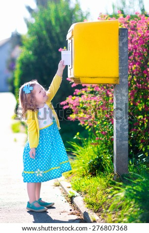 Little girl with an envelope at post office. Child sending letter. Kid throwing card into a mail box. Postal service in Germany, Europe. Delivery and shipment at outdoor mailbox. - stock photo