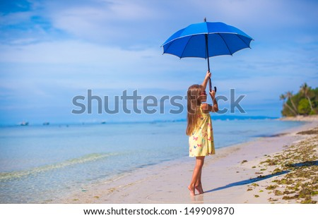 little girl with an umbrella in hands on her toes on the sandy white beach - stock photo