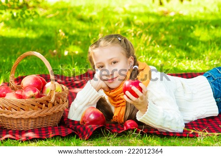 Little girl with apples in autumn park