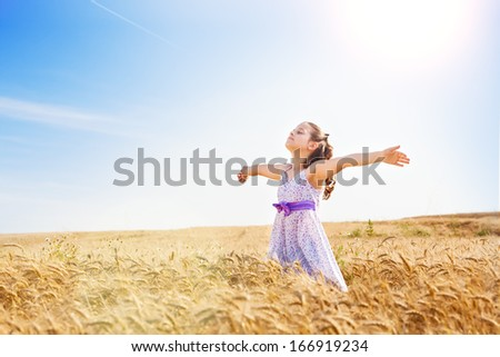 Little girl with arms outstretched in a wheat field,copy space.Flare light - stock photo