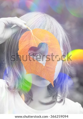 little girl with autumnal leaf - stock photo