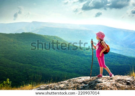 Little girl with backpack standing on cliff edge looks into the distance. Landscape composition. Travel, lifestyle concept. - stock photo