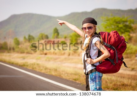 little girl with backpack standing on the road and showing on mountain - stock photo