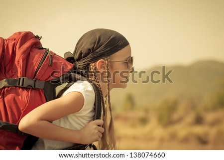 little girl with backpack walking on the road - stock photo