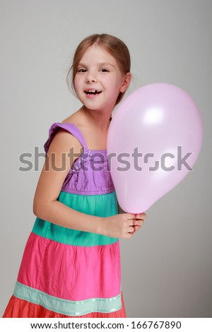 Little girl with balloons on a gray background