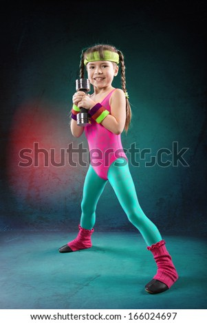 Little  girl with barbells at fitness exercise