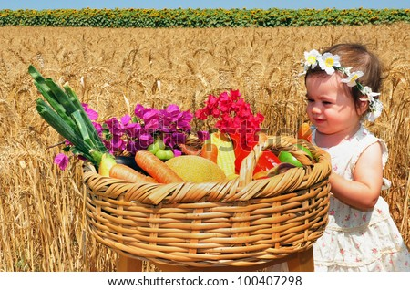 Little girl with basket of the first fruits during the Jewish holiday, Shavuot in Israel. - stock photo