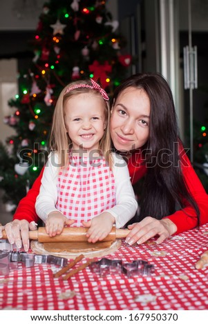 Little girl with beautiful mother baking Christmas gingerbread cookies together
