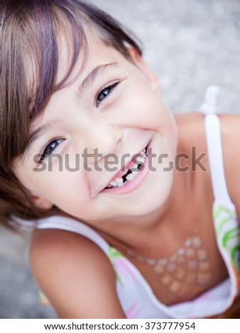 Little girl with big smile and missing milk teeth - stock photo