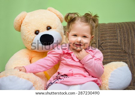 Little girl with big teddy bear sitting on sofa in the living room at home