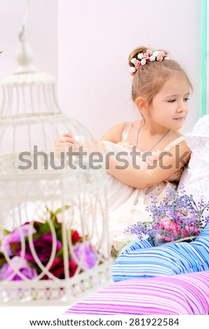 little girl with birdcage and flowers in home interior