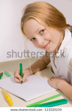 little girl with blond hair draws