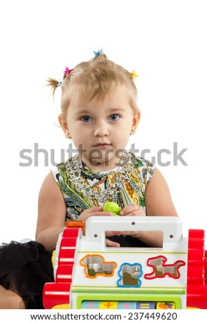 Little girl with blond hair sitting and playing with toys isolated on white background - stock photo