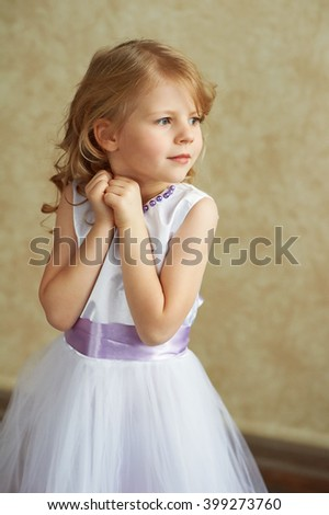Little girl with blond hair standing on a light background and looking to the right