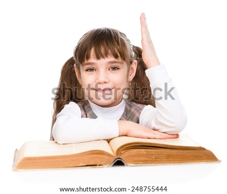little girl with book raising hand knowing the answer to the question. isolated on white background