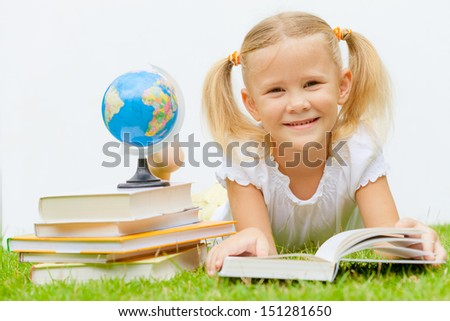 little girl with books lying on the grass - stock photo