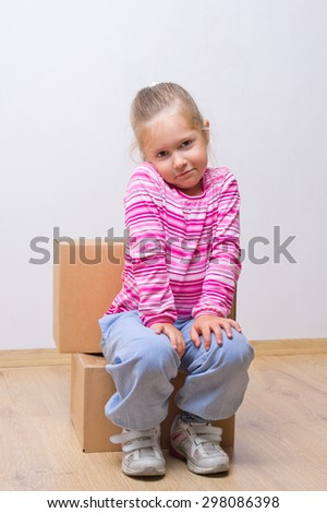 Little girl with boxes on the floor - stock photo