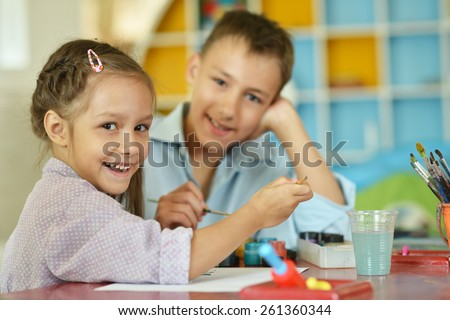 Little girl with boy drawing at home - stock photo