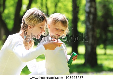 Little girl with bubbles with mom