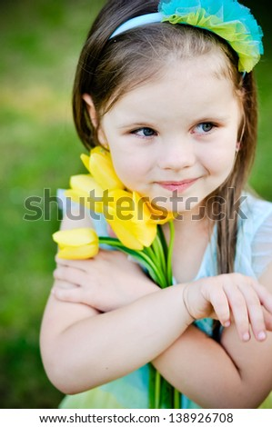 Little girl with bunch of yellow tulips outdoors - stock photo