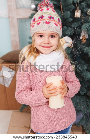 Little girl with candles around the Christmas tree