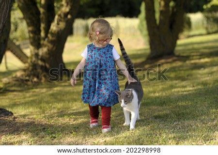 little girl with cat, outdoors in the garden - stock photo