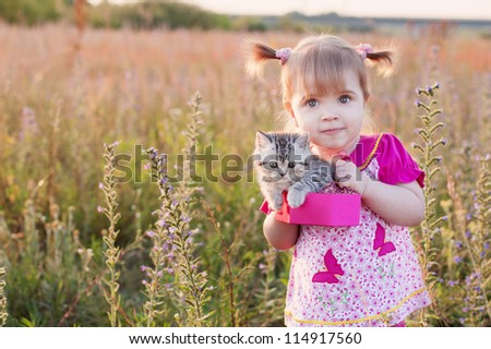 little girl with cats in basket outdoor