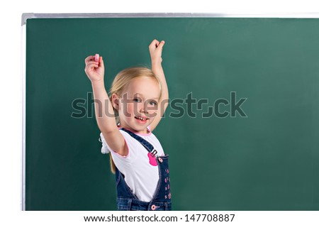 little girl with chalk in hand up, standing near blackboard on white background