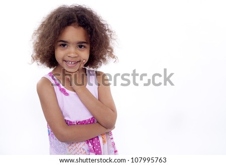 Little girl with chin on hand smiling at camera.