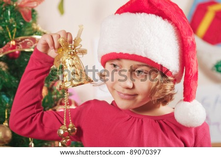 little girl with christmas bell and spruce tree