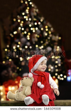 little girl with christmas hat and teddy bear on black background