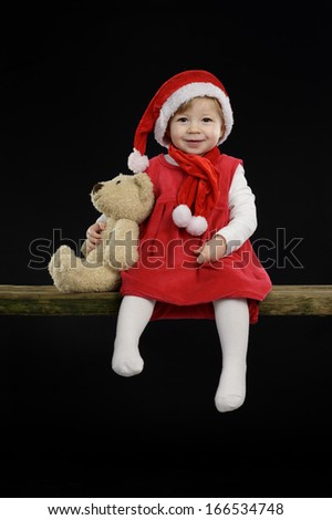 little girl with christmas hat and teddy bear on black background - stock photo