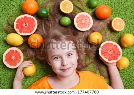 Little girl with citrus fruit lying on the grass - stock photo