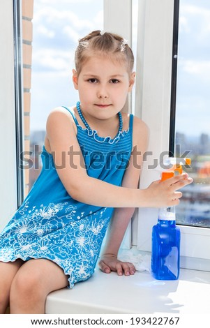 Little girl with cleaner for windows sitting on windowsill