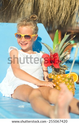 Little girl with cocktail on the beach vacation.