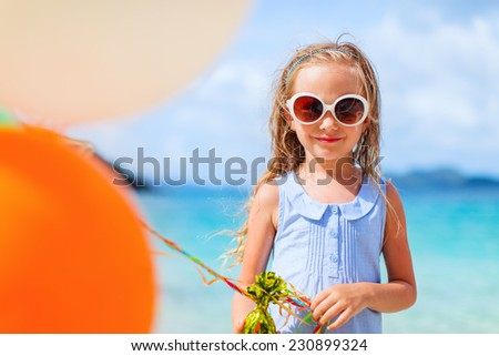 Little girl with colorful balloons at beach during summer vacation - stock photo