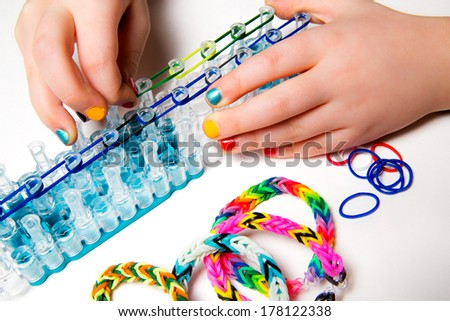 Little girl with colorful nails making a rubber loom bracelet with a hook . Hands close up. Young fashion concept  - stock photo