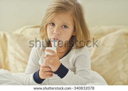 little girl with cough using inhaler at home - stock photo