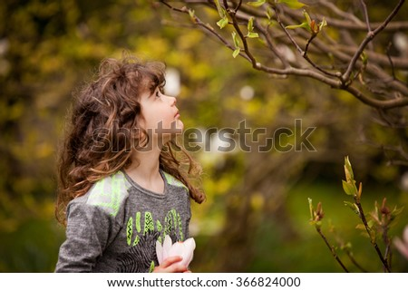 Little girl with curly hair playing in the garden - stock photo