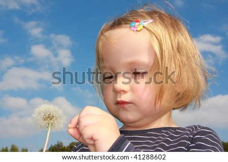 little girl with dandelion under blue sky
