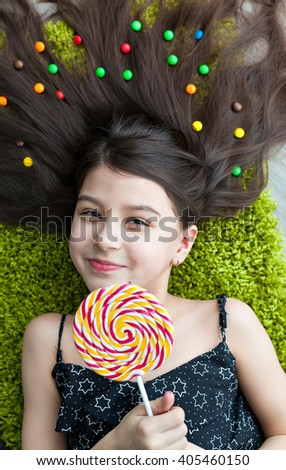 Little girl with dark hair lying on the floor among the sweets. Many candies in her hair. smile, joy and emotion on the face of the child. Top view of a big yellow and pink lollipops in hands.  - stock photo