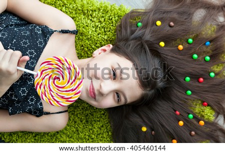 Little girl with dark hair lying on the floor among the sweets. Top view of a big yellow and pink lollipops in hands.  smile, joy and emotion on the face of the child. Many candies in her hair. - stock photo