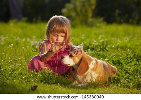 Little girl with dog in the garden - stock photo