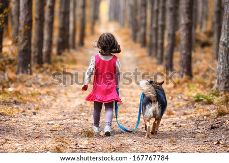Little girl with dog walking on the road. Back to camera. - stock photo