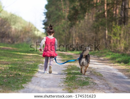 Little girl with dog walking on the road near forest back to camera