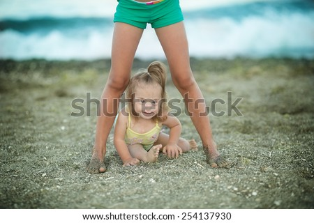 little girl with Down syndrome crawling between the legs sisters - stock photo