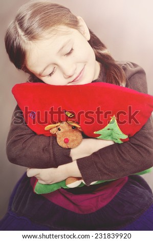 Little girl with eyes closed and decorative pillow with Christmas deer and Christmas tree. Little girl enjoys Christmas time. - stock photo