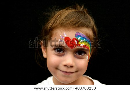 Little girl with face painted with rainbow. - stock photo